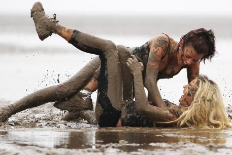 Dos luchadoras recién caídas tras una lluvia de barro